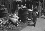 Jasper Wood Collection: Boys walking by trash barrels