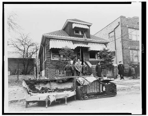 [Exterior view of home of Malcolm X, in foreground remains of charred furniture]