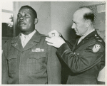 Colonel R. L. Salzmann pins a first Lieutenant's bar on the shoulder of African American Lieutenant Jesse J. Holbert