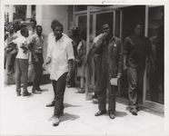 Mississippi State Sovereignty Commission photograph of Willie Ricks dressed in overalls and standing with a group of young African American males on a sidewalk in Jackson, Mississippi, 1964 June