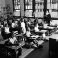 Students seated at desks, raising their hands as a young girl recites and a nun observes in a classroom at Nazareth Catholic Mission in Montgomery, Alabama..