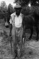 Farm scenes: Don Stuart Farm. Vicksburg, Miss. Don Stuart cultivating cotton, house exterior, barn, smokehouse, henhouse, mules and dogs (FSP C-68 #511)