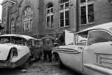 Fire fighters and damaged cars in the street after the bombing of 16th Street Baptist Church in Birmingham, Alabama.