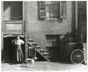African-American woman and dog standing in front of an unidentified flat. (Detail of SNDC 7-09-0034a).