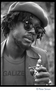Peter Tosh: portrait wearing beret, dark glasses, and a Legalize it tee shirt, smoking a pipe