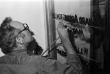 Man painting Richard Arrington's name on the door to the mayor's office in Birmingham, Alabama.