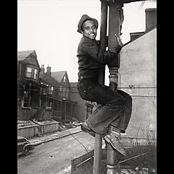 Man climbing wooden pillar of house porch