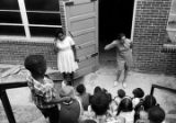 Two women speaking to children seated on the steps outside a brick building, possibly during a summer program.
