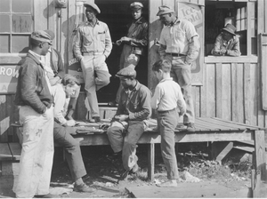 "Migrants playing checkers (with bottle caps), on a juke joint porch after a ""freeze-out"" of vegetable crops. Near Okeechobee, Florida"