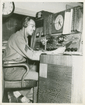 African American Sargeant Julius C. McKenzie, Station Manager of WABS (the Hospital Program Distribution System at Aberdeen Proving Ground), seated at microphone and holding a record, Maryland