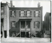 African-American woman and dog standing in front of an unidentified flat.