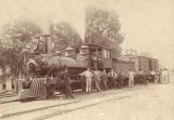 Group standing in front train, probably part of the Southern Railway.