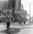 Firemen with hoses outside the Carver Theatre during a the Children's Crusade in downtown Birmingham, Alabama.