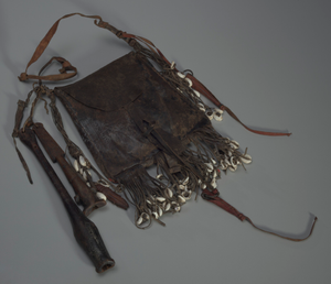 Leather bag with tools, whistles, and shells