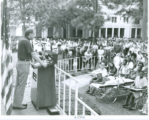 Photograph of Georgia governor Jimmy Carter speaking at a podium to a large gathering of patients, staff, and local residents at the Georgia Warm Springs Foundation, Warm Springs, Meriwether County, Georgia, 1971-1975?