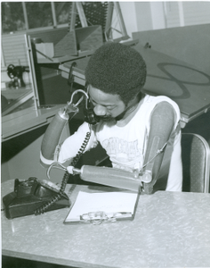 Photograph of a double amputee using his prosthesis to dial a telephone at the Georgia Warm Springs Foundation, Warm Springs, Meriwether County, Georgia, 1965-1975