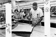 A man cuts a stack of fabric in a garment shop