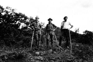 Three unidentified men with walking sticks.