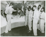 "Man pointing to a ""Survival Museum"" diorama of a soldier sitting under a makeshift bunker in the snow, while African American soldiers from the 25th Regimental Combat Team look on, Pensacola Naval Air Station, Florida"