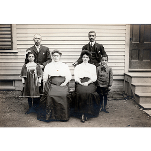 Family portrait, group of six pose in front of house