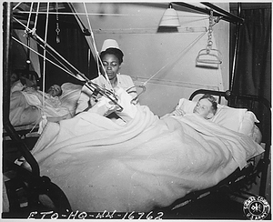 """Lt. Florie E. Gant...tends a patient at a prisoner-of war hospital somewhere in England."""