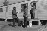 Recruiter interviewing family outside a mobile home.
