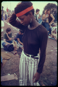 Young African American woman with a headband and striped pants at the Woodstock Festival