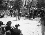 Governor Frank Dixon standing at a microphone on the campus of Tuskegee Institute, probably preparing to introduce President Franklin D. Roosevelt to the audience.