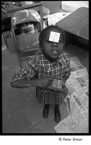 Young girl with box of chalk and sticker on her forehead, the Liberation School