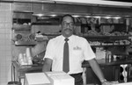 Chicken Charlie's restaurant manager posing behind the counter, Los Angeles, 1987