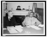 [Clarence Mitchell (right) sitting at table with unidentified man, three men sitting next to fireplace in the background]