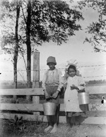African American boy and girl holding milking pails
