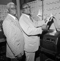 John LeFlore and another man checking the Democratic primary election results from an Associated Pres teleprinter in Mobile, Alabama.
