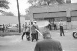 Firemen spraying adolescent civil rights demonstrators with a hose during the Children's Crusade in downtown Birmingham, Alabama.