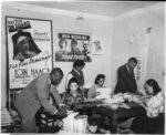 [NAACP branch office, Detroit, Mich., view showing two men and four women working at desks and membership posters on the wall]