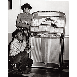 A boy and a girl listening to a jukebox