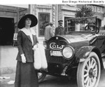 Edith Story standing in front of her Cole automobile, with her chauffeur in the background