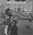 Black boy playing on swings