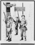 Three National Guardsmen stand guard under a Los Angeles city limits sign in the southern end of the riot torn section of the city