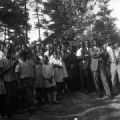 Audience listening to Martin Luther King Jr. speak in a wooded area in Alabama.