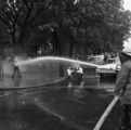 Firemen spraying a civil rights demonstrator with a hose at Kelly Ingram Park during the Children's Crusade in downtown Birmingham, Alabama.