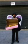 Unidentified man holding an open pastry box posing in front of a mural depicting angel wings