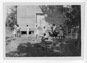 Photograph of African American women and children sweeping and raking land by a wooden building, Clarkesville, Habersham County, Georgia, 1953