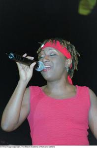 Sherida Sharpe singing into microphone Ashe Caribbean Dance