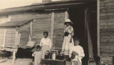 African American women and children with jars of preserves in front of a cabin in Madison County, Alabama.