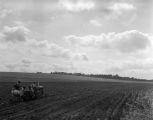 Men using a tractor and other equipment to prepare a field in Autauga County, Alabama, for planting.