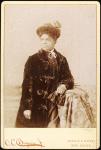 Studio portrait of woman wearing hat, and velvet coat