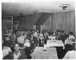 Male and female patrons seated at white cloth covered tables, Slim Jenkins nightclub Oakland, California