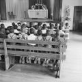Children kneeling in pews in the chapel at Nazareth Catholic Mission in Montgomery, Alabama.