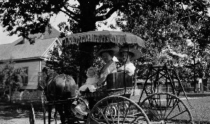 Unidentified women with baby in horse drawn buggy.